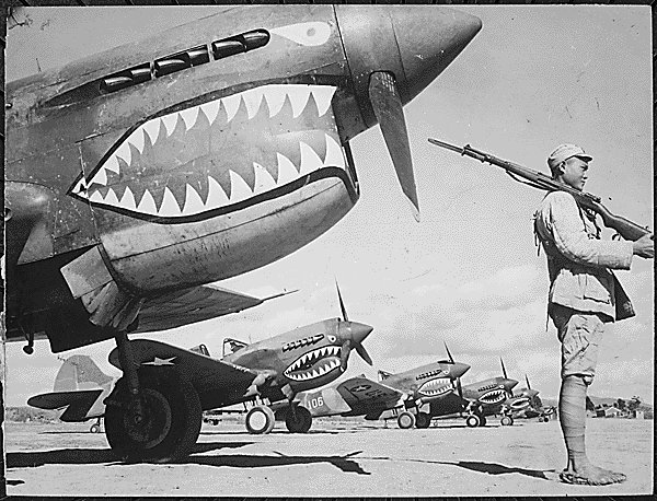 A Chinese soldier guards a line of American P-40 fighter planes...