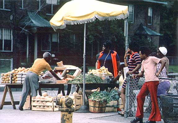 Black sidewalk salesmen arranging their fresh fruits and vegetables on Chicago`s South Side. June 1973 (NWDNS-412-DA-13759) National Archives and Records Administration