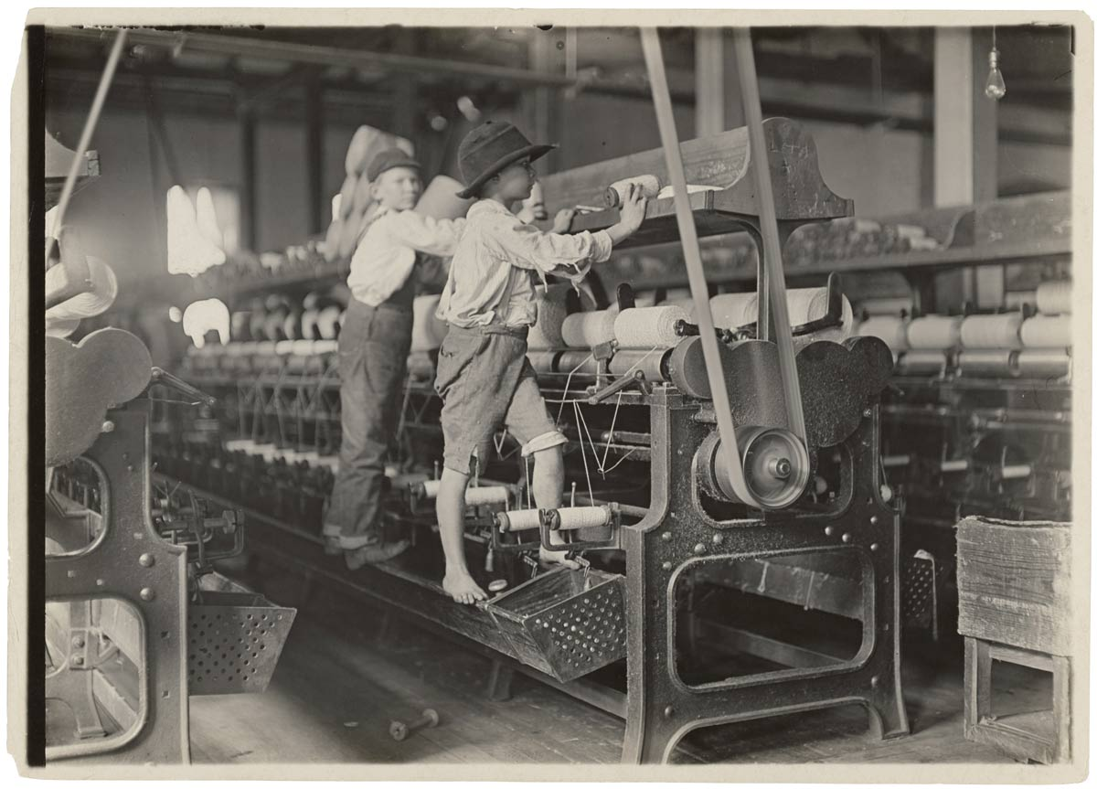 Photo Image of two boys working a clothing mill