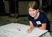 A young visitor 'joins the signers' by adding her name to a facsimile Declaration of Independence at the National Archives' July 4, 2002 celebration at Union Station, Washington, DC