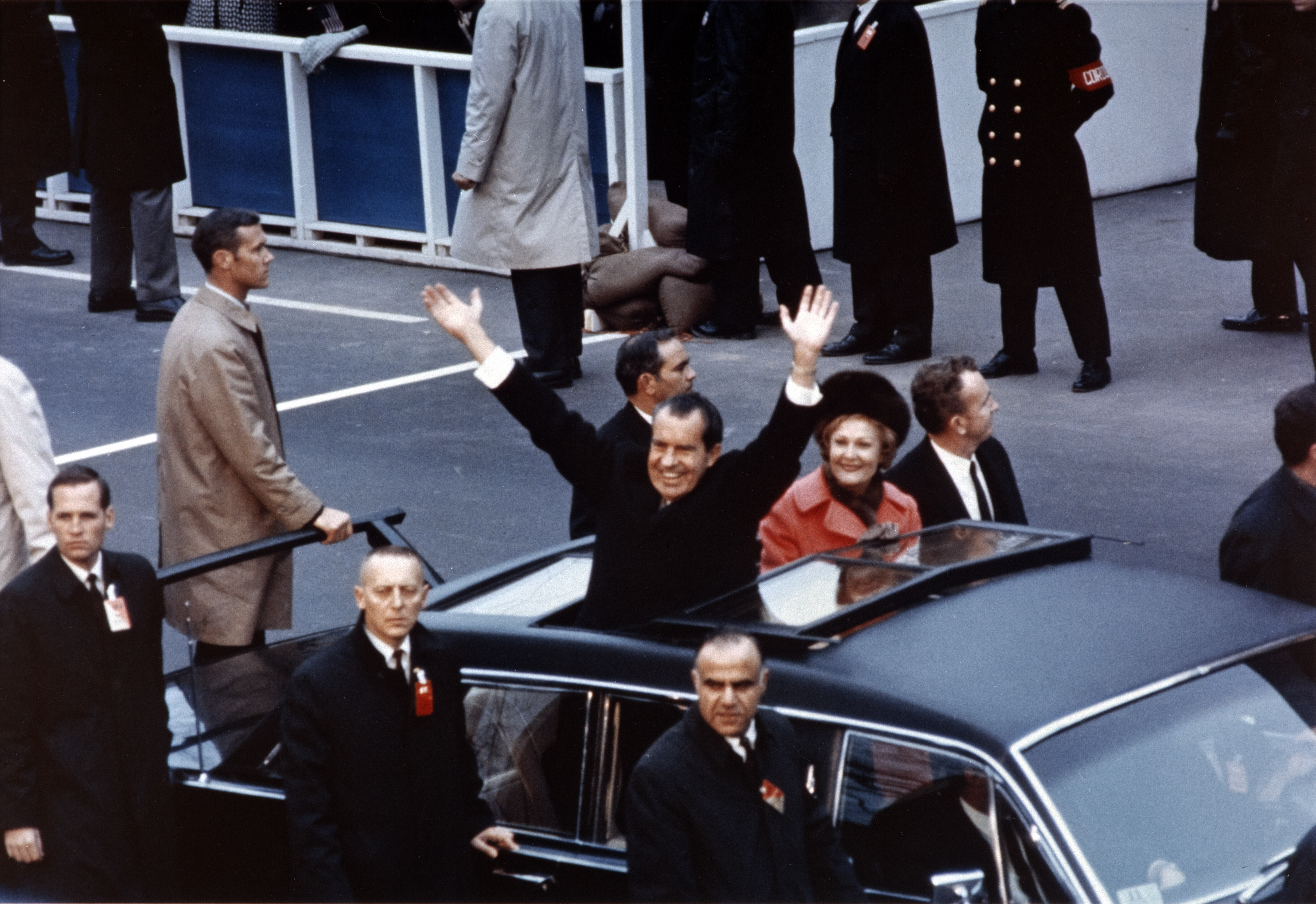 President Richard Nixon and First Lady Pat Nixon wave from the Presidential limousine in the inaugural motorcade