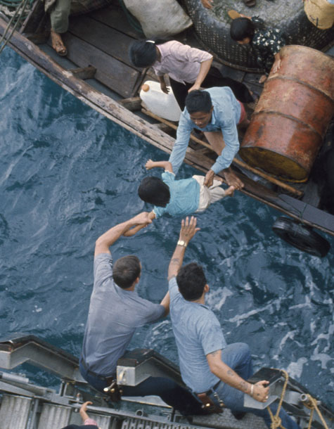Crewmen of the amphibious cargo ship USS Durham take Vietnamese refugees from a small craft in the South China Sea, 1975,National Archives, General Records of the Department of the Navy