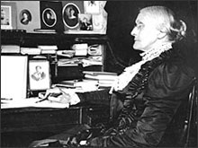 Susan B. Anthony sitting at desk with pen in hand.