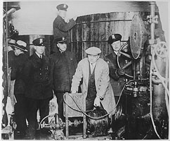 Detroit police inspecting equipment found in a clandestine underground brewery during the prohibition era
