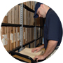 man opening a file folder in a file room