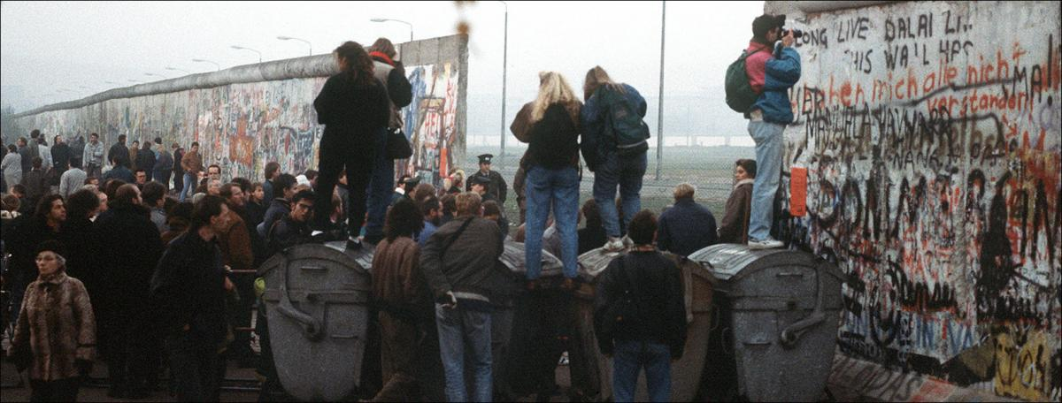 People look through the broken Berlin Wall