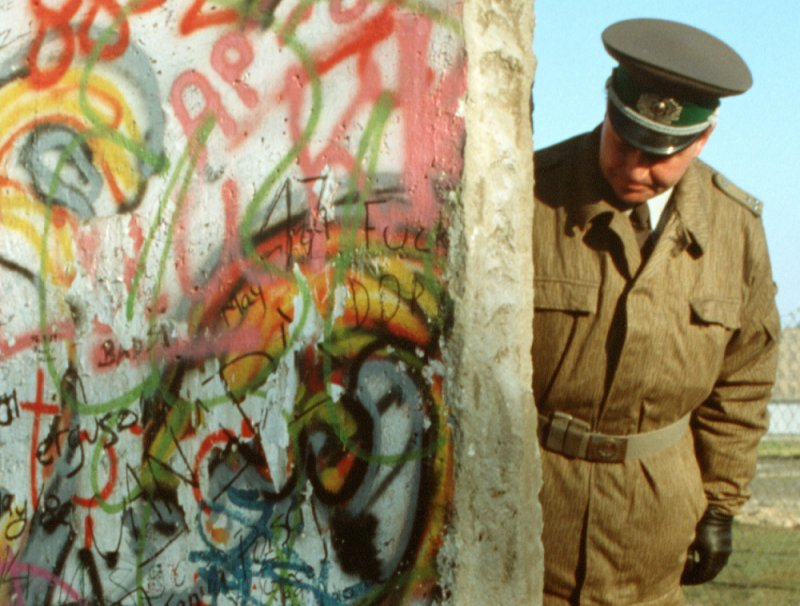 East German policeman looks at broken section of the Berlin Wall