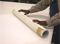 A cover paper is being rolled onto the tube to protect originals from light damage
