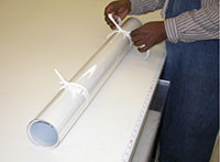 Cotton twill tape or flat ribbon being loosely tied around the roll to secure the polyester film
