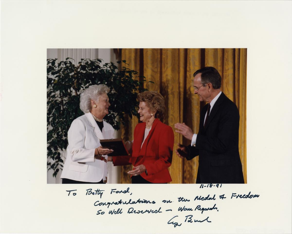 "Betty Ford receives the Presidential Medal of Freedom from President George H. W. Bush and First Lady Barbara Bush. The citation honored her for providing ""selfless, strong, and refreshing leadership on a number of issues."" November 18, 1991"