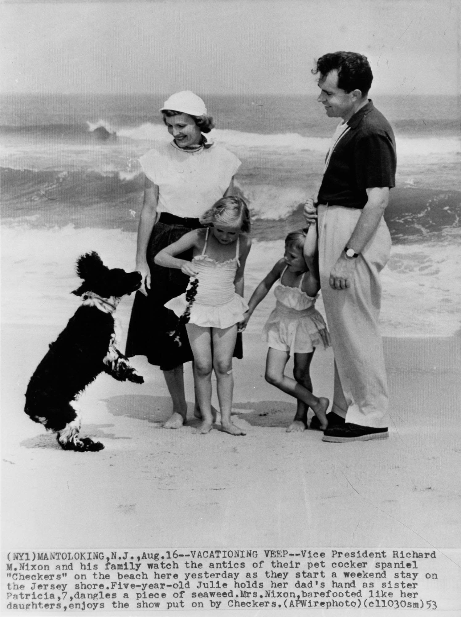 Vice-President Richard Nixon, with wife Pat and daughters Tricia and Julie, watch the antics of their pet cocker spaniel