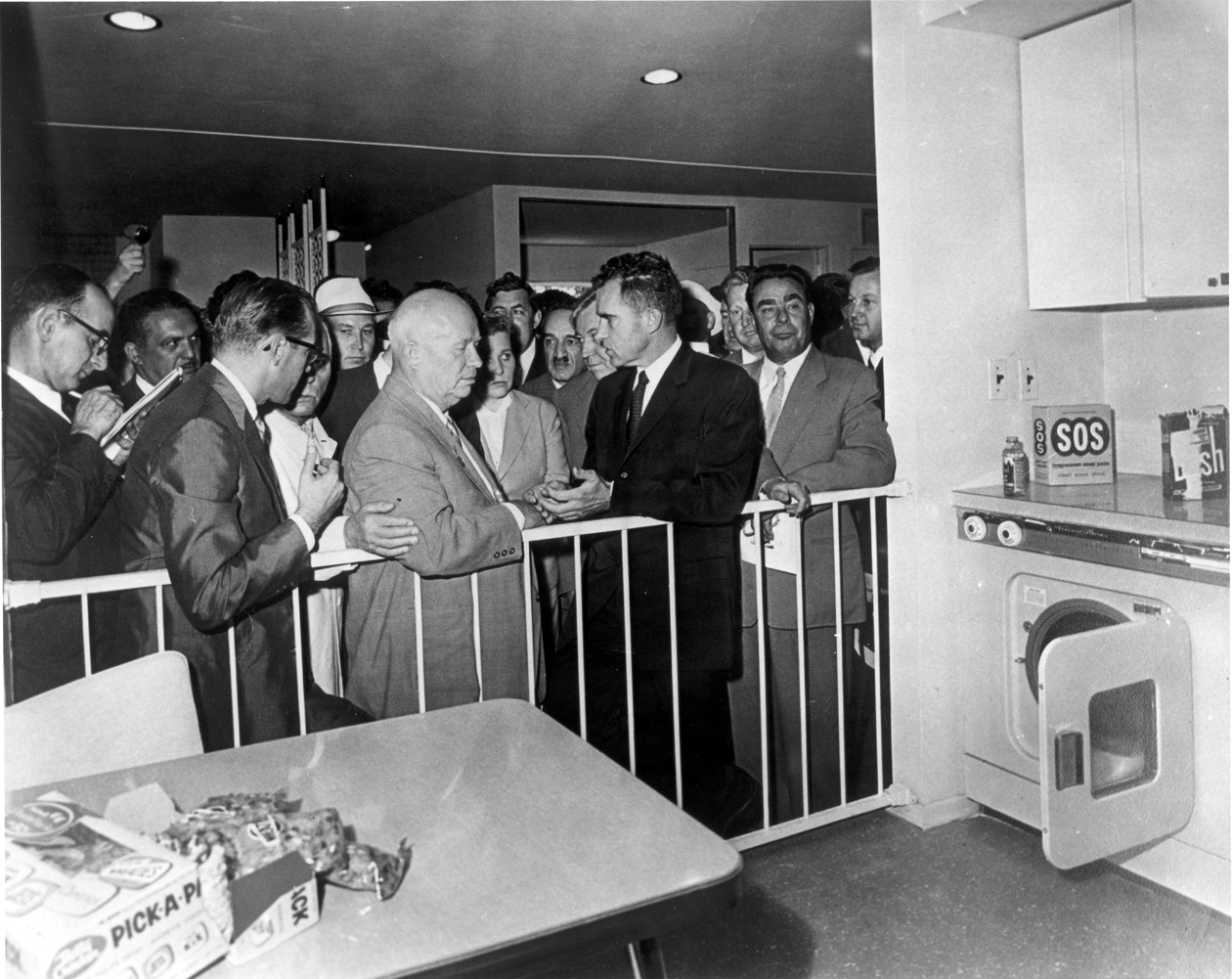 Vice-President Nixon spars with Premier Khrushchev before reporters and onlookers, including Politburo member Leonid Brezhnev at the American National Exhibition at Sokolniki Park, in Moscow, 1959. Nixon and Khrushchev are photographed in front of a kitchen display – the impromptu exchanges came to be known as the Kitchen Debate, July 24, 1959. Richard Nixon Presidential Library and Museum, used with permission of the Richard Nixon Foundation and Julie Nixon Eisenhower.