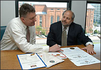 Two men look at electoral certificates at the Federal Register