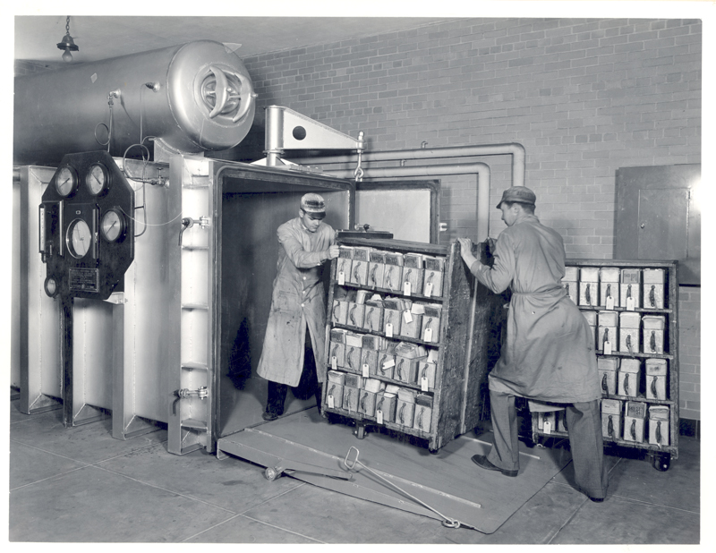 Archives workers push a cart of Veterans Administration records into a vacuum chamber for fumigation in June 1936