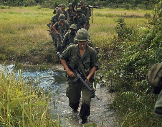 Soldiers marching through a rice paddy