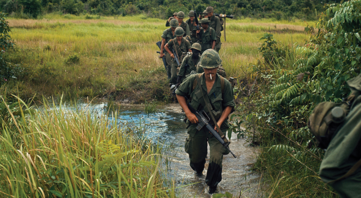 Solider's marching through a rice paddy Members of Company B, 1st Battalion, 27th Infantry Regiment (Wolfhounds), 25th Infantry Division, cross a stream approximately 9.3 miles southeast of Nui Ba Den during search-and-clear operations near Fire Support Base. (National Archives, RG 111)