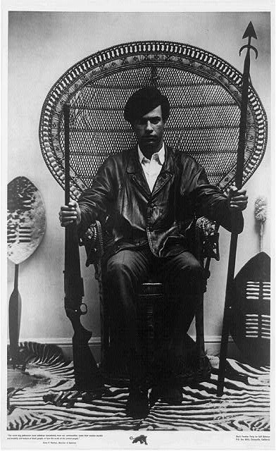 Huey Newton seated in rattan chair holding a rifle and spear