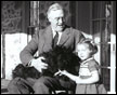 Franklin Delano Roosevelt in his Wheelchair with Fala and Ruthie Bie at Top Cottage, Hyde Park, New York, 02/1941.