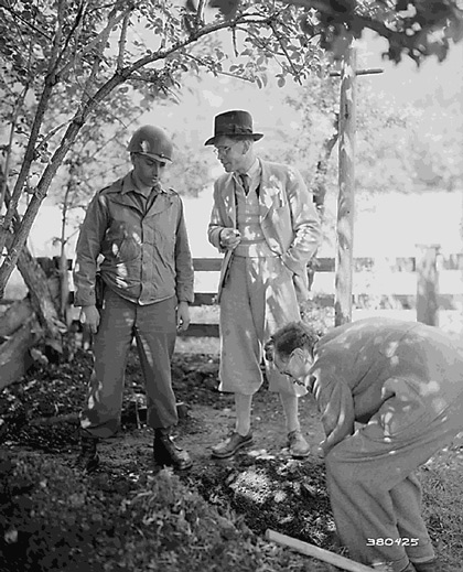 SS Major Kurt Baron Haller Von Hallerstein admitted that he had buried nearly a million dollars worth of securities and jewelry near Garmisch, Germany.  Hallerstein (center) watches with Tec 4 Frederick Wolinsky, New York, NY, as his brother Helmuth Baron Haller Von Hallerstein, digs. May 25, 1945