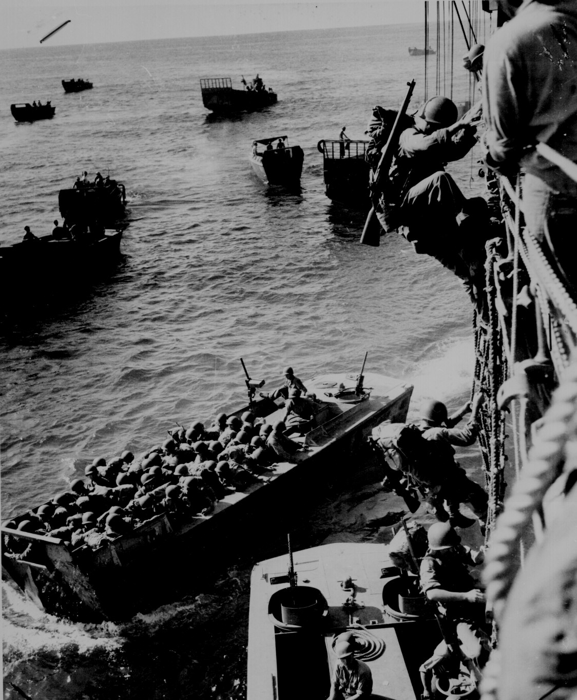 """U.S. troops go over the side of a Coast Guard manned combat transport to enter the landing barges at Empress Augusta Bay, Bougainville, as the invasion gets under way."" November 1943."