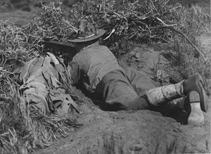 Soldier of the 63rd. Regt. Inf. camouflaged and dug in a concealed rifle pit with his rapid fire new model French Chauchat rifle