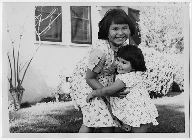 Two young Navajo girls embracing