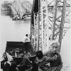 The old and the young flee Tet offensive fighting in Hue, managing to reach the south shore of the Perfume River despite this blown bridge.