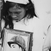 Young widow with photo of her missing husband, at mass funeral service for Tet victims in Hue