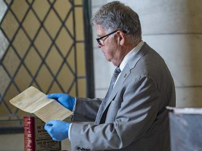 Archivist David Ferriero examines a document from the Arlington Cemetery time capsule