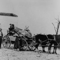 13. A refugee family leaving a war area with belongings loaded on a cart.