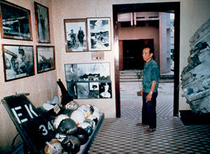 A Vietnamese visitor to Hanoi's Military Museum stands in a room with photographs and war memorabilia