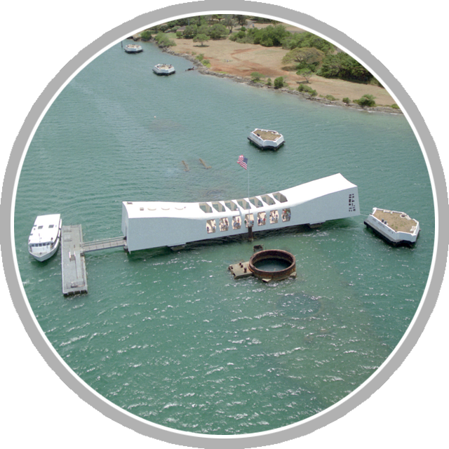 An aerial view of the USS ARIZONA Memorial at the northeast end of Ford Island, with markers in the background indicating battleships lost during the Japanese attack on Pearl Harbor on December 7, 1941